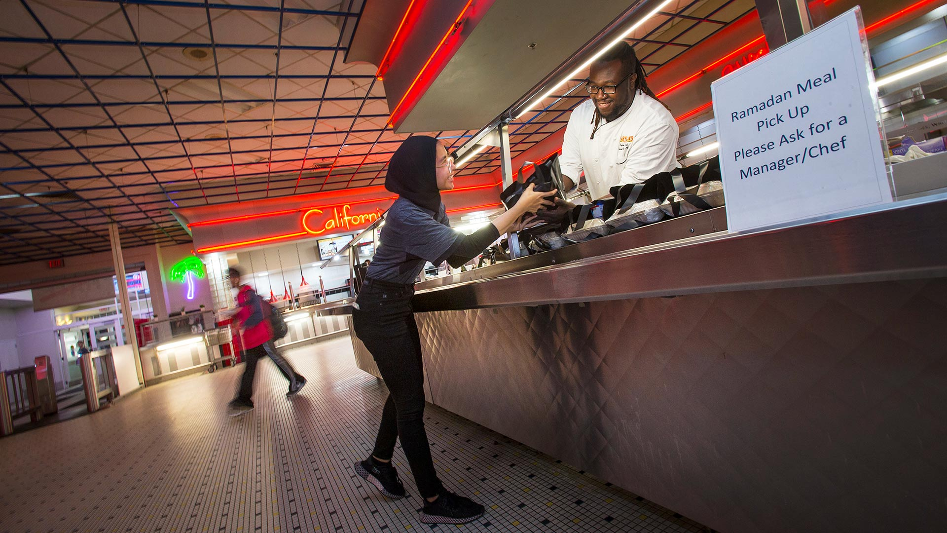 Nur Sulaiman '19 picks up a Ramadan meal from Dining Services Executive Sous Chef Byron Scott last night in the Diner. (Photo by John T. Consoli)