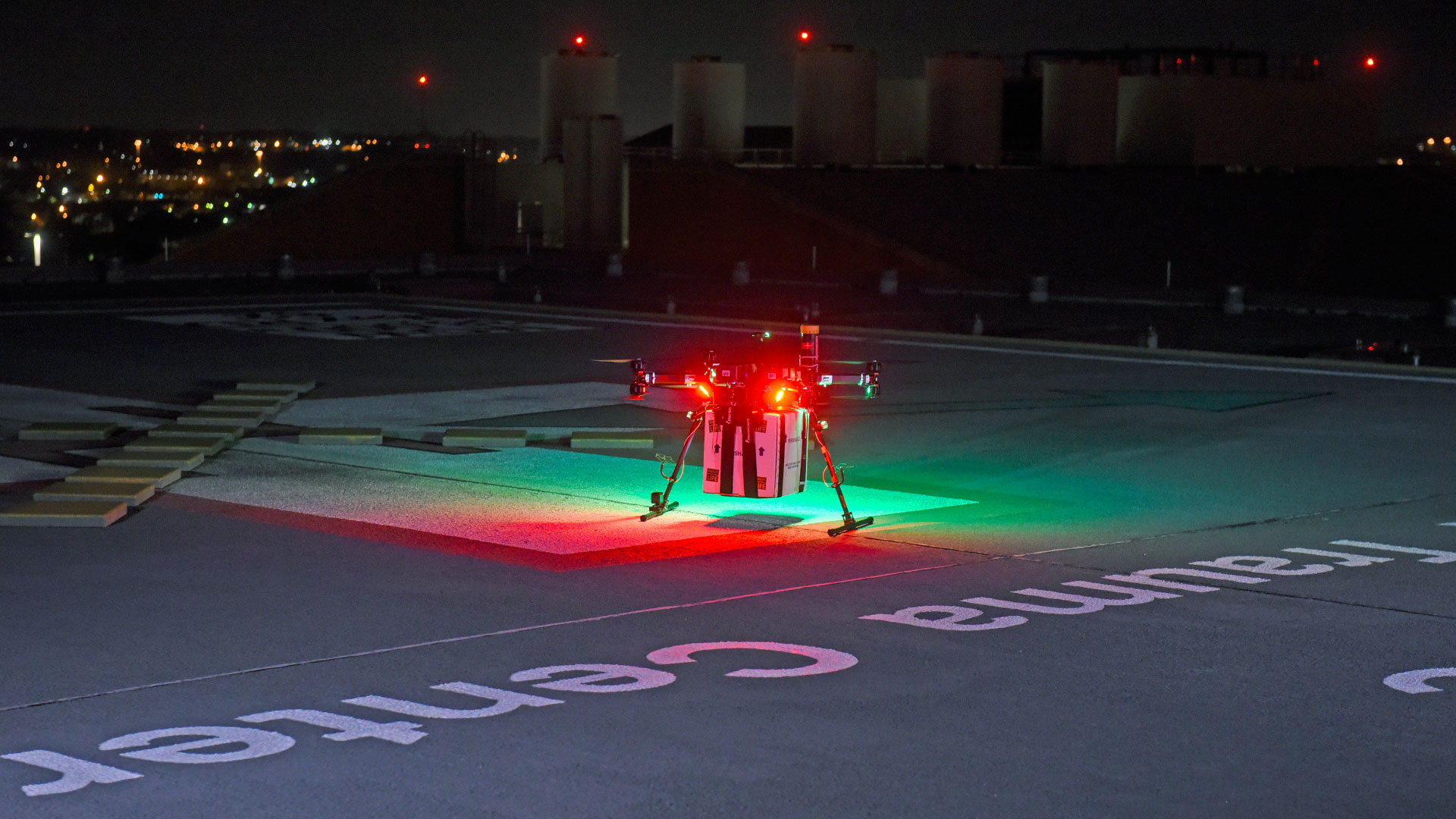 An aerial drone siting on a landing pad at night, with green and red lights. A cube shaped container is attached to the underside of the drone chassis.