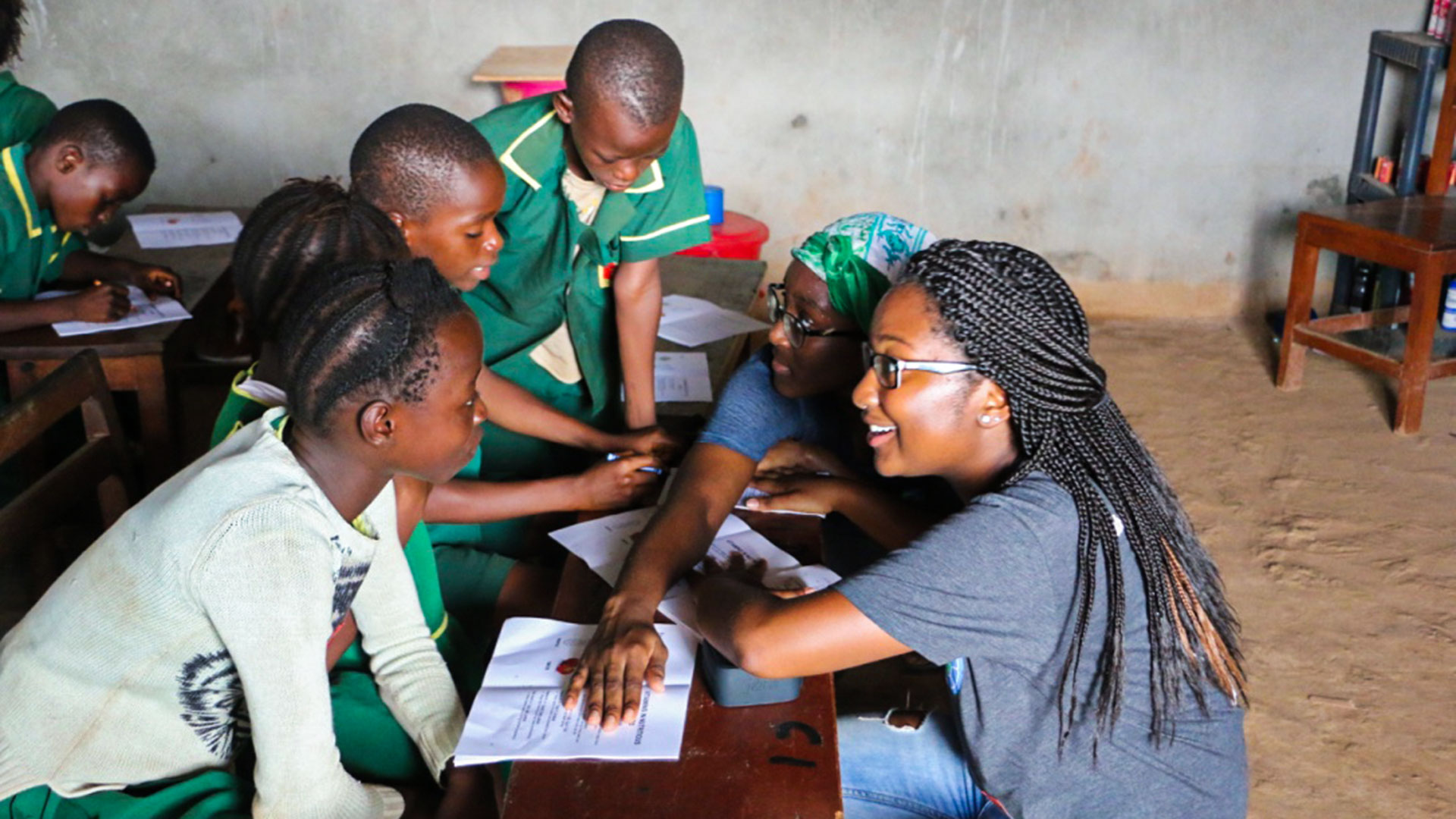 As part of Public Health Without Borders, Kelsie Challenger, a behavioral and community health major, interacts with students in Calaba Town, Sierra Leone. Inspired by such work, School of Public Health Professor Pamela I. Clark (below) made a $1.15 million gift to support the Global Health Initiative. (Photo courtesy of the School of Public Health; Clark headshot by John T. Consoli)